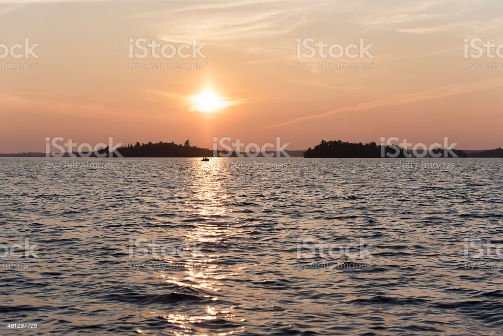 Sunset and fishing boat on a lake. stock photo