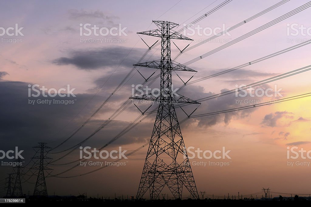 Sunset and high voltage pylons tower royalty-free stock photo