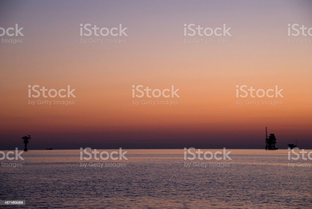 sunset and offshore platforms stock photo