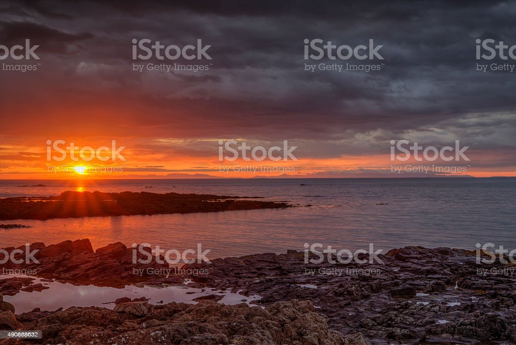 Sunset and rough rocky coast stock photo