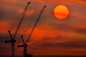 sunset and silhouette of the crane operating