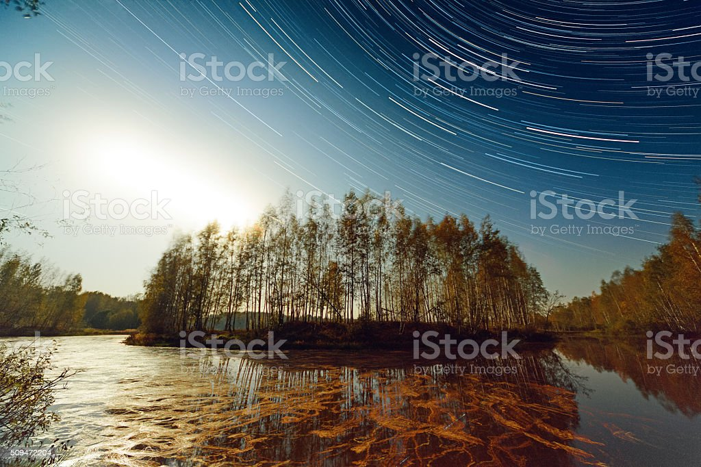 Sunset and Star Trails Over Lake stock photo