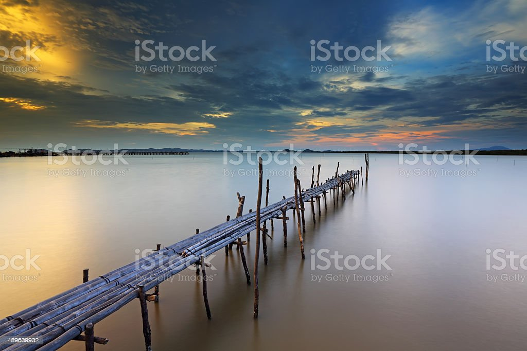 Sunset at bamboo bridge on sea stock photo