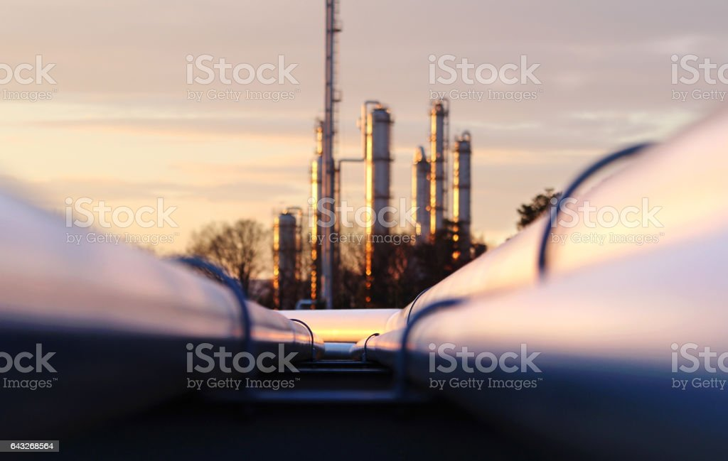 sunset at crude oil refinery with pipeline network stock photo