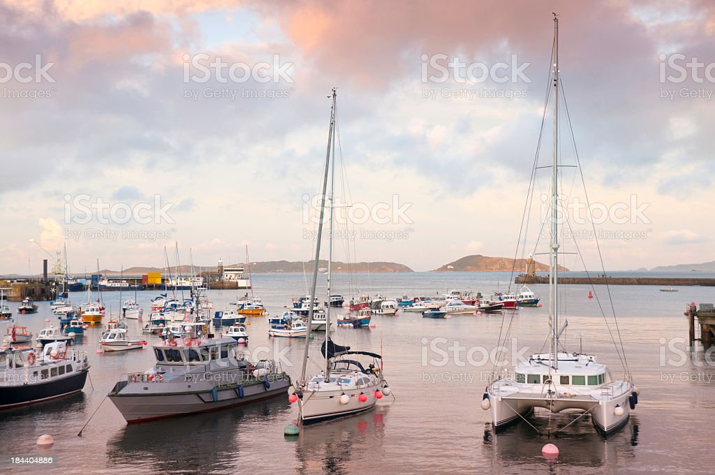 Sunset at harbour with fishing boats and lighthouses stock photo