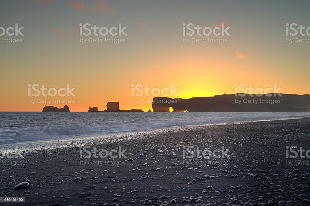 Sunset at Kirkjufjara beach and Dyrholaey rock stock photo