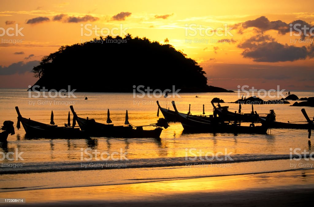 Sunset at Phuket beach with silhouettes of boats and island stock photo