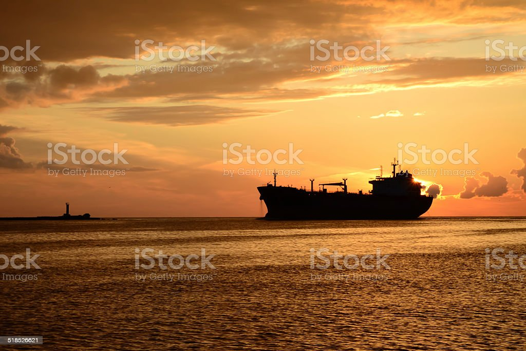sunset at pier and a passing ship stock photo
