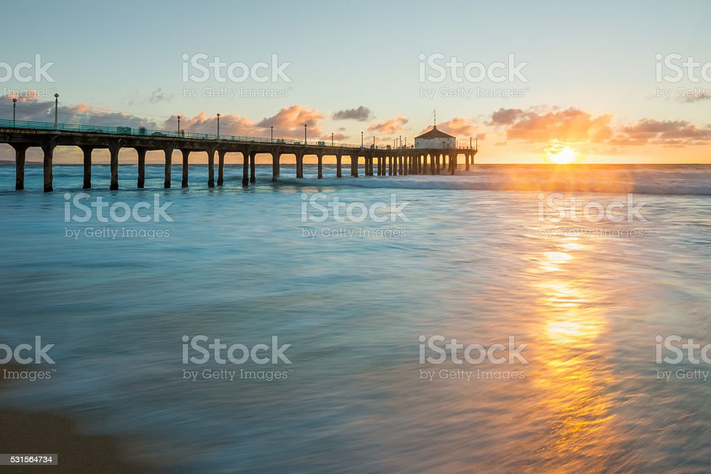 Sunset at Pier on Ocean with Water Rushing to Beach stock photo