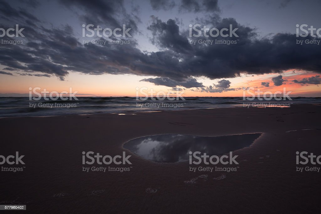 Sunset at the beach with clouds reflections stock photo