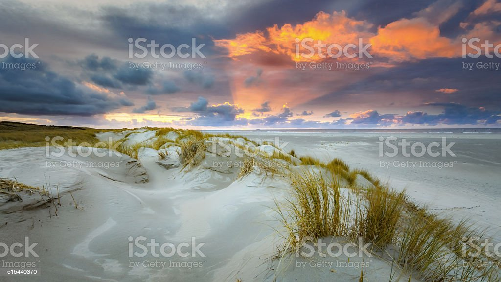 Sunset at the beach with dunes and clouds stock photo