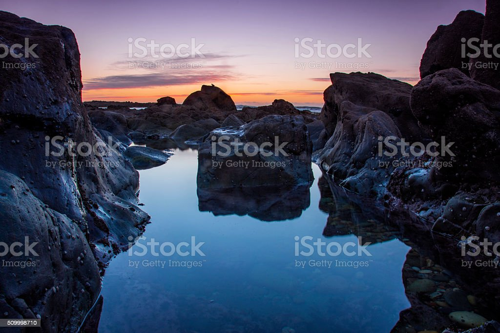 Sunset at the beach with rocks and the sea stock photo