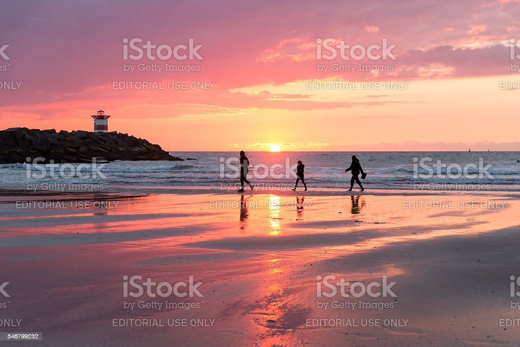 Sunset at the Dutch coast near Scheveningen with passing walkers stock photo