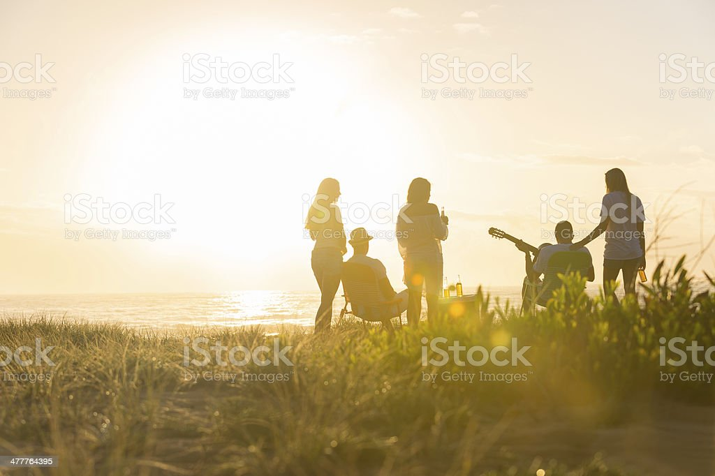 Sunset Beach party with a group of friends royalty-free stock photo
