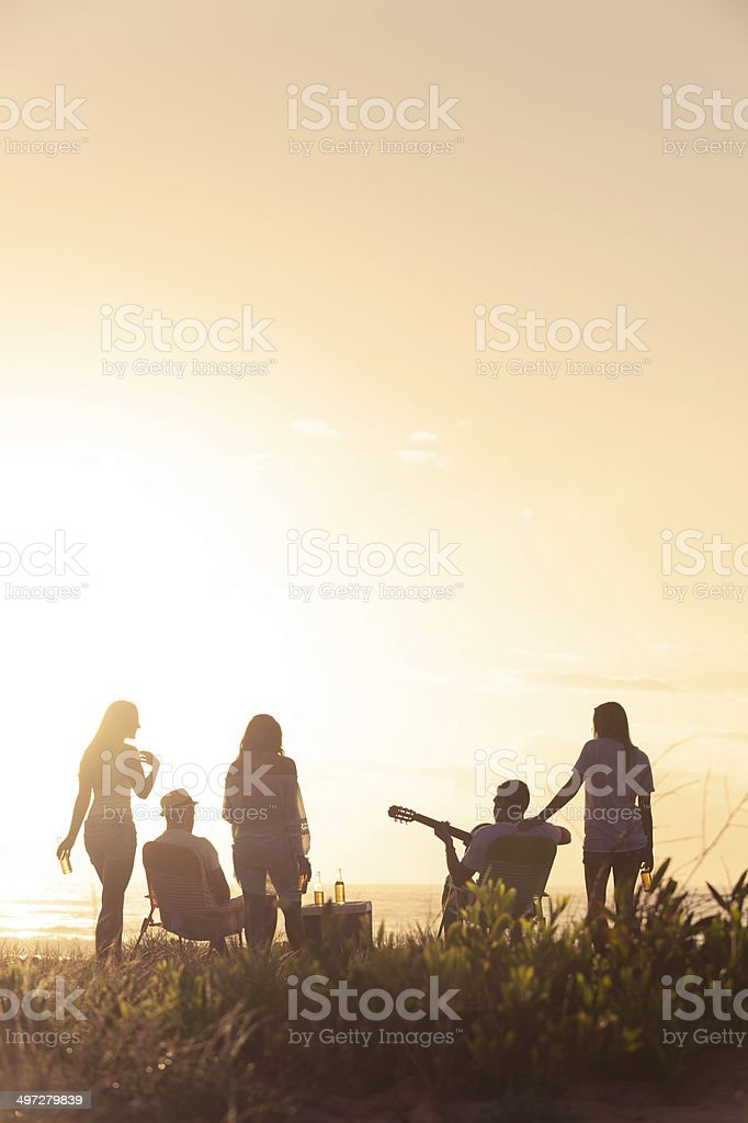 Sunset Beach party with a group of friends stock photo