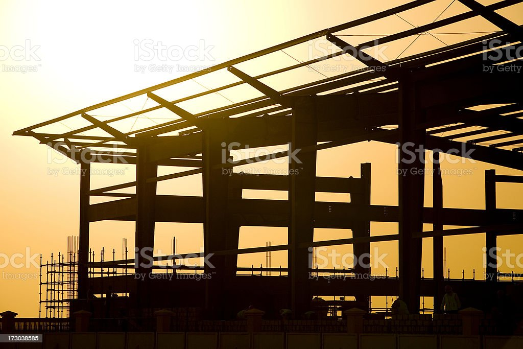 Sunset behind a construction site for large building royalty-free stock photo