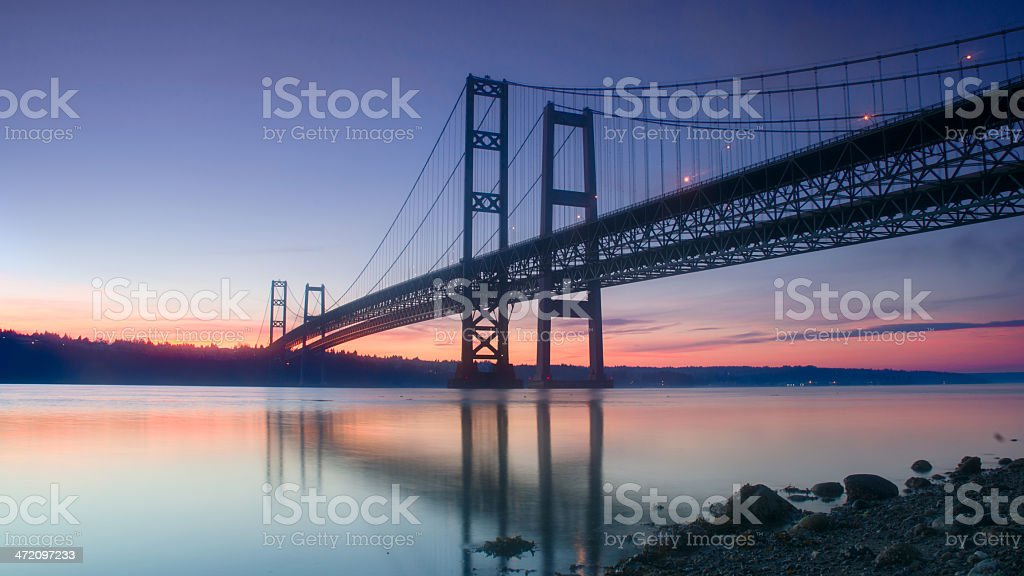 Sunset behind a dark bridge with still waters stock photo