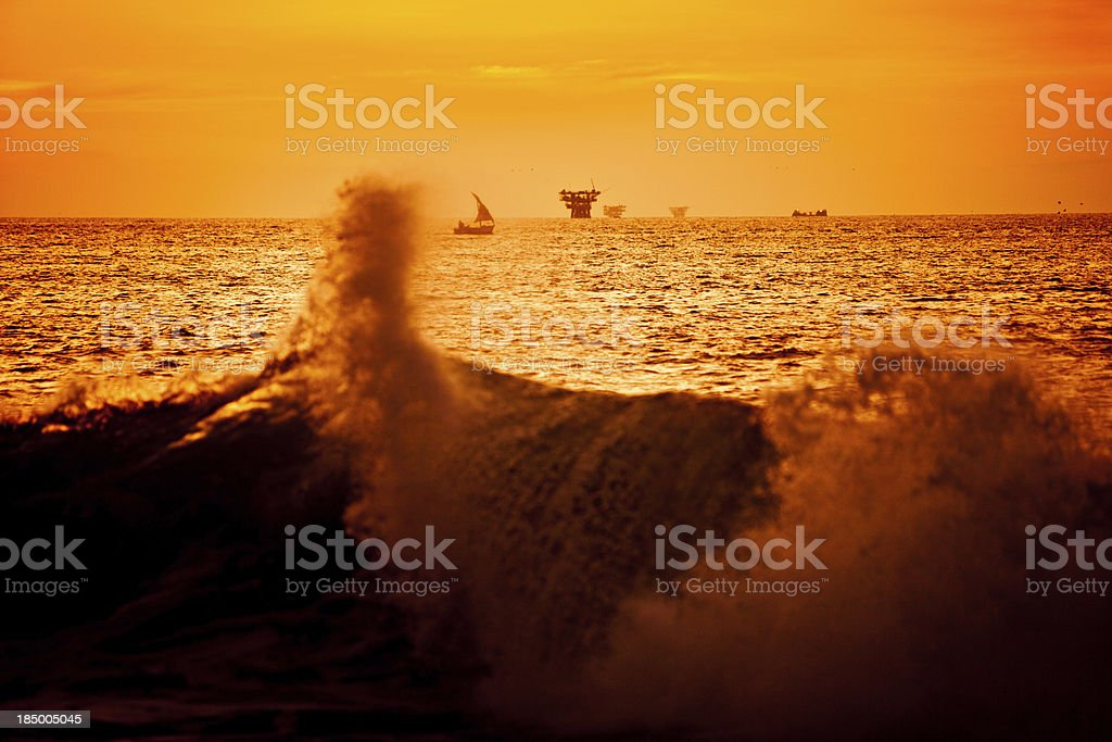 Sunset behind an oil platform in the Pacific Ocean royalty-free stock photo