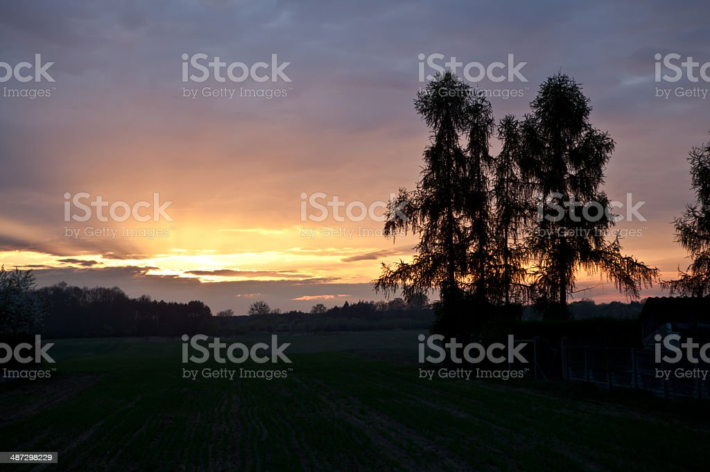 sunset behind clouds royalty-free stock photo