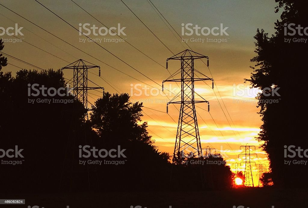 Sunset behind electric power lines stock photo