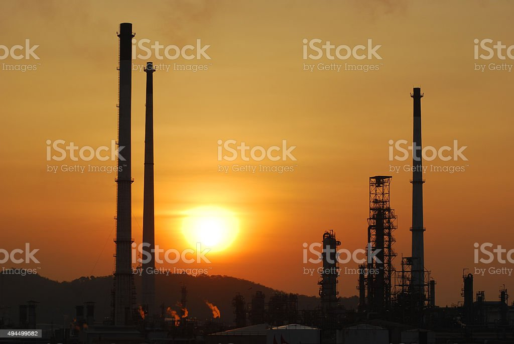 Sunset behind oil refinery plant stock photo