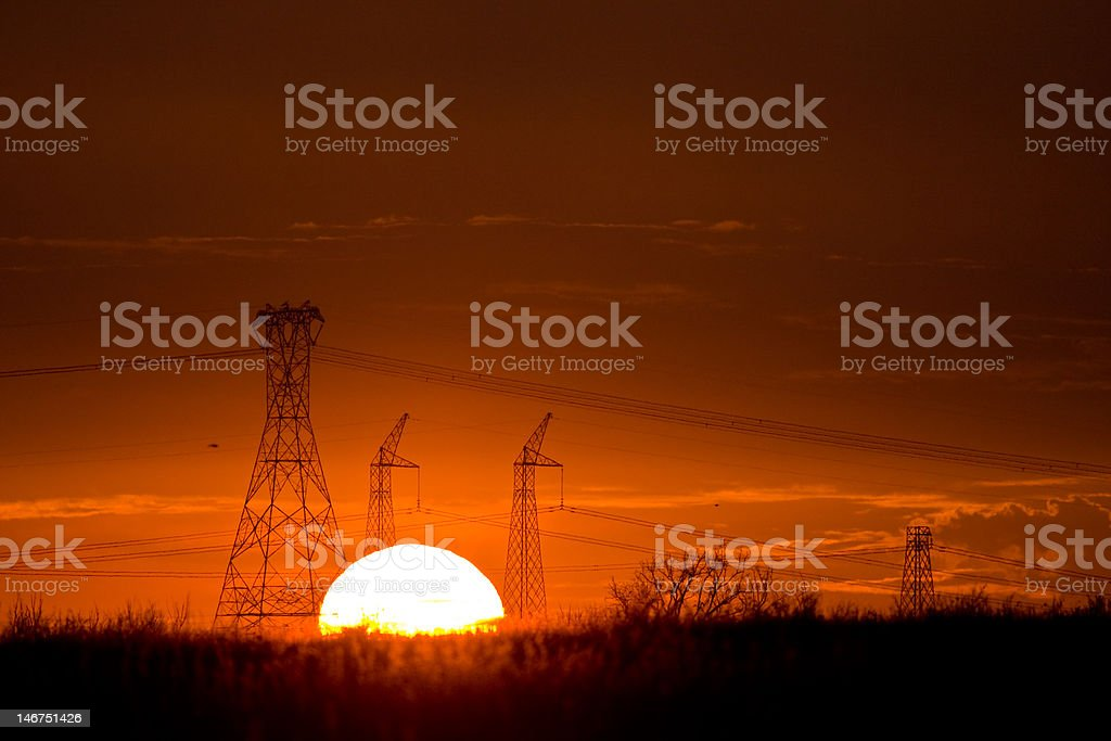 Sunset behind powerlines stock photo