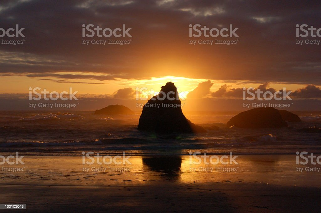 Sunset behind rock on beach royalty-free stock photo