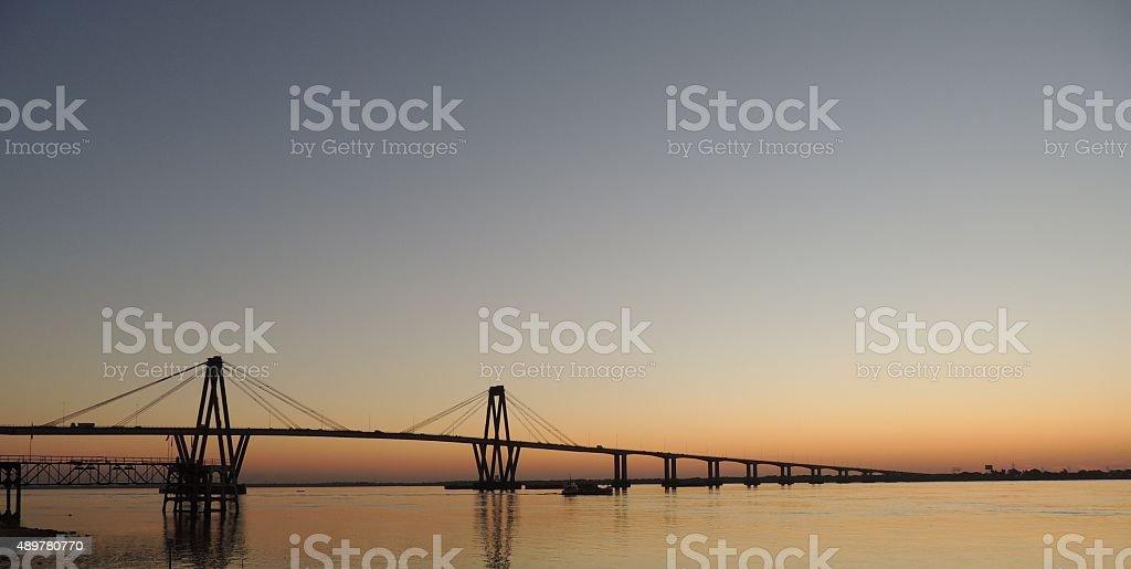 sunset behind the bridge on Parana river stock photo