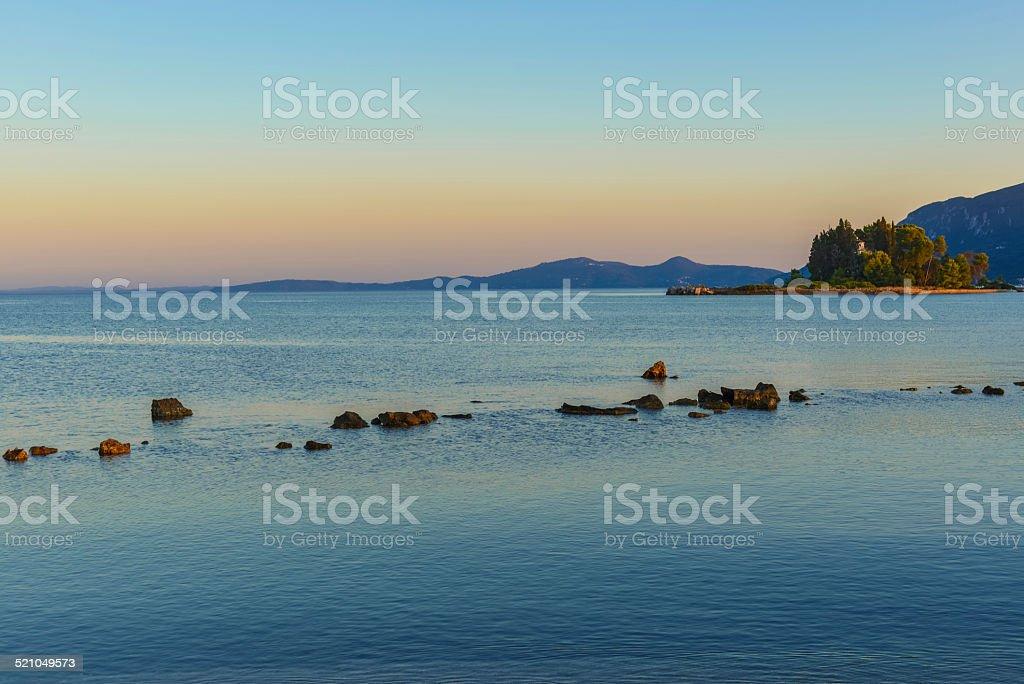 Sunset behind the Pontikonisi island at Corfu Greece stock photo