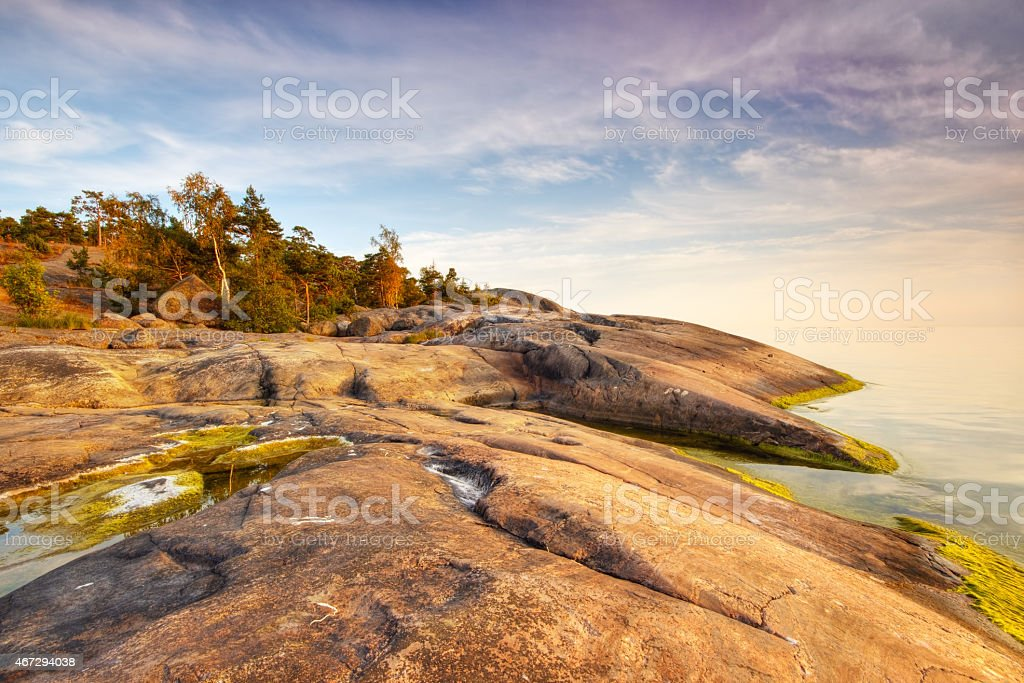 Sunset colored beach rock with still water royalty-free stock photo