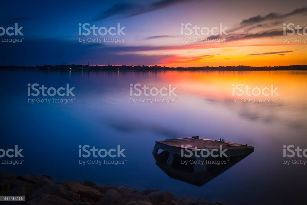 Sunset colours illuminate clouds reflected perfectly in Poole Harbour stock photo