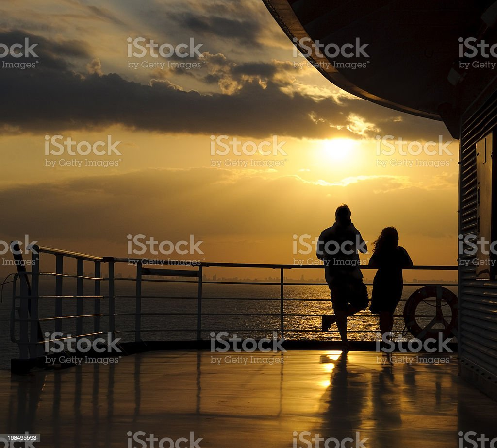 A silhouetted man and woman watching the sunset at sea. The skyline...