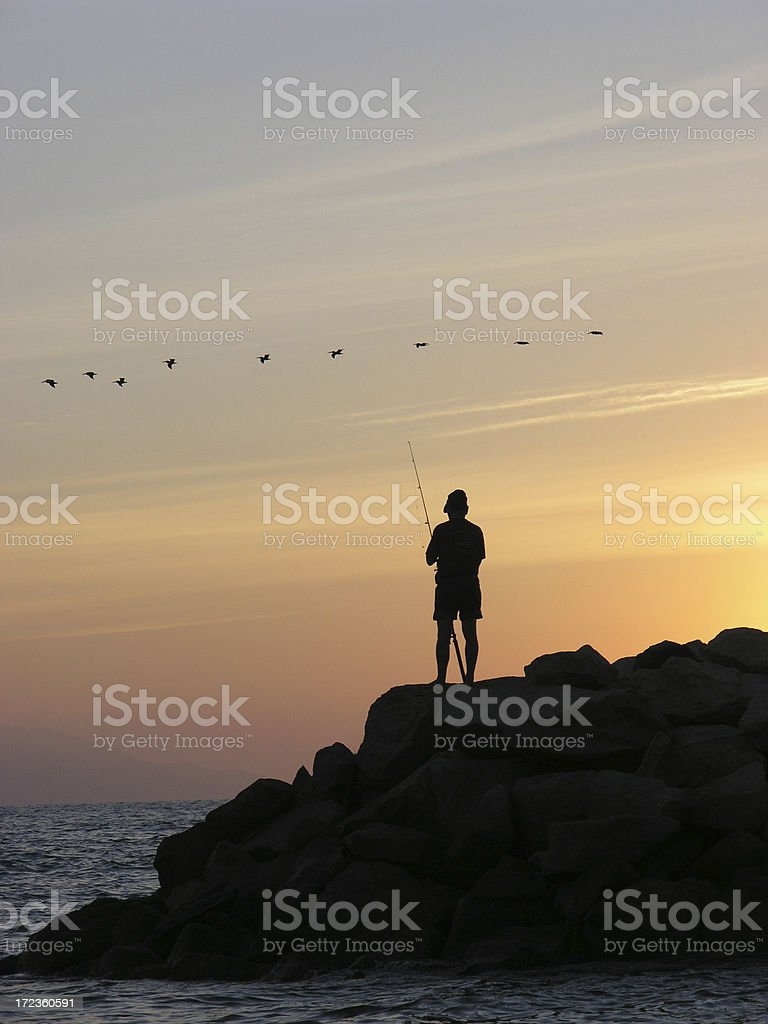 Sunset Fisherman with Birds stock photo