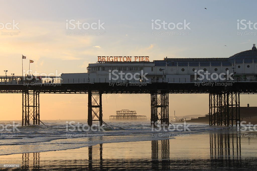 Sunset from Brighton West Pier to Brighton Palace Pier stock photo