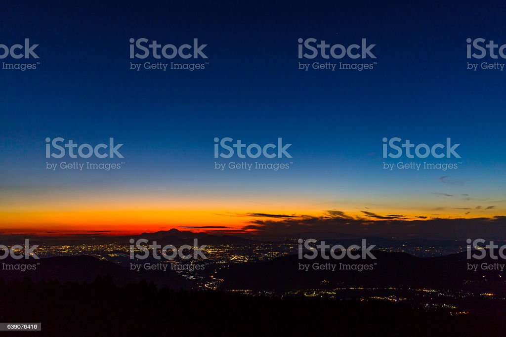 sunset glow in the city against the mountains stock photo