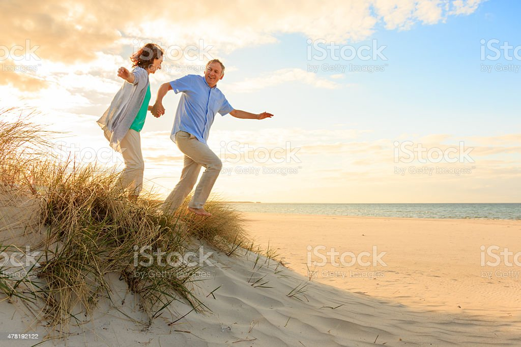 Sunset – happy mature couple at beach stock photo