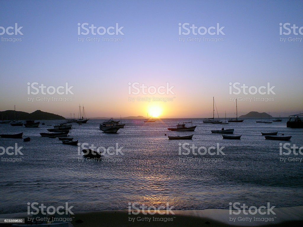 Sunset in Buzios beach with boats in Brazil stock photo