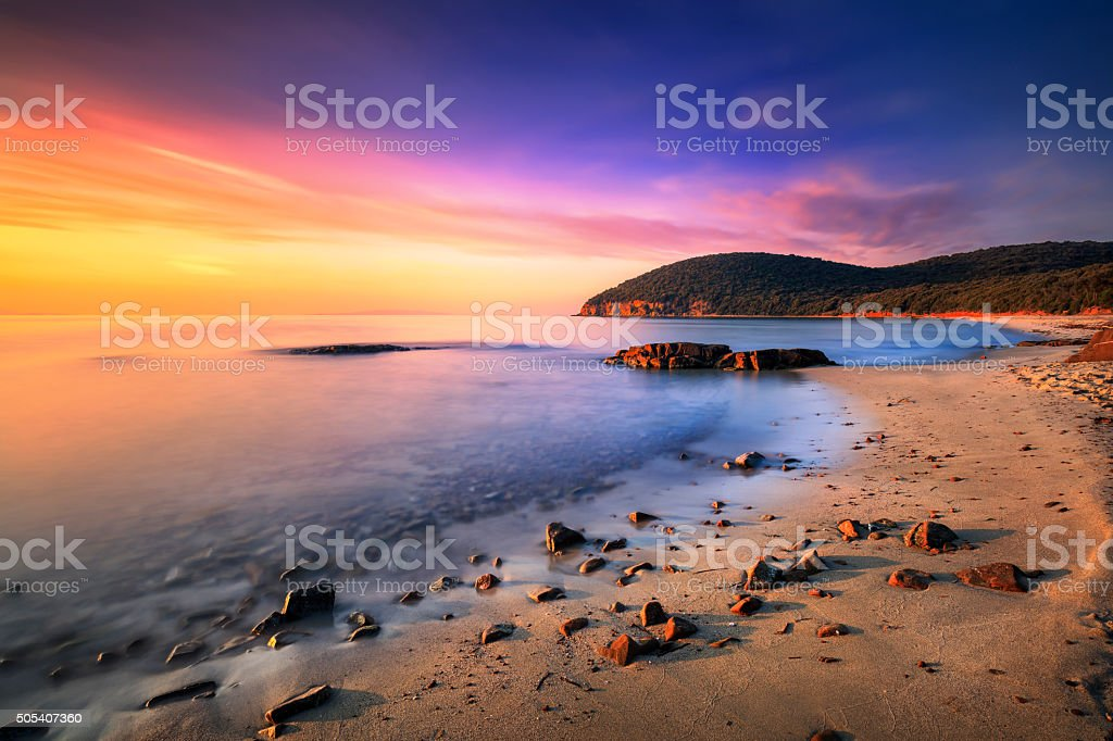 Sunset in Cala Violina bay beach in Maremma, Tuscany. Mediterran stock photo