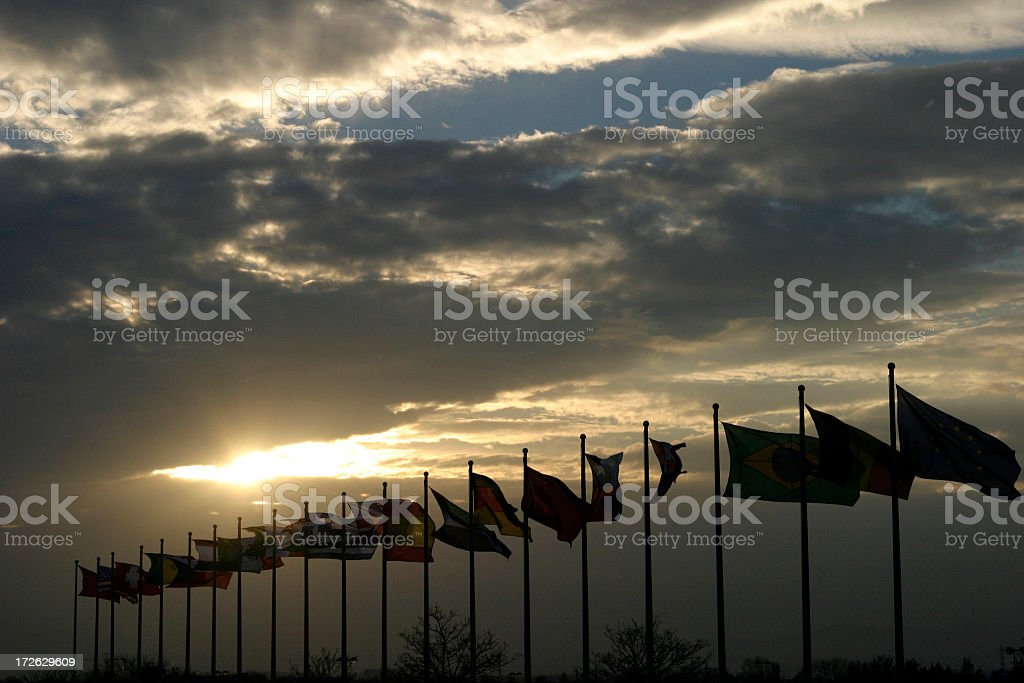 Sunset in cloudy sky beyond a row of flags stock photo