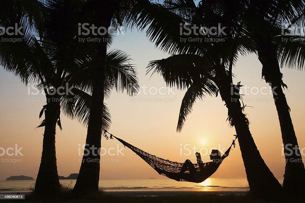 sunset in hammock on the beach stock photo