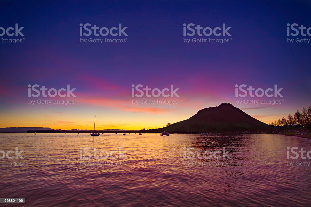 Sunset in harbour with boats and mountain stock photo