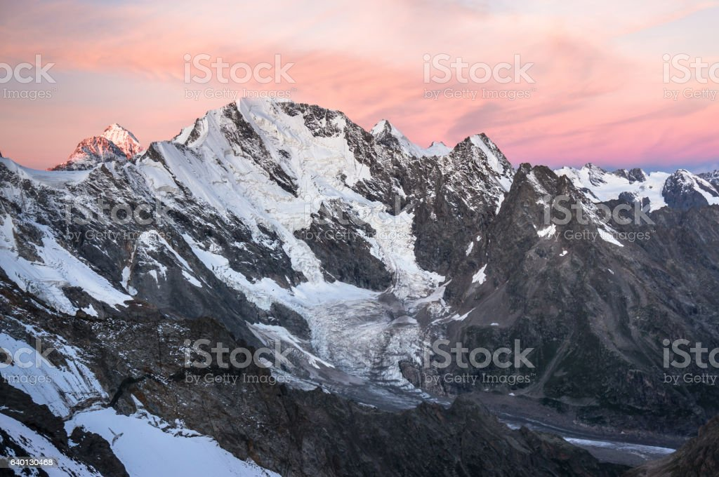Sunset in high snowy mountains. stock photo