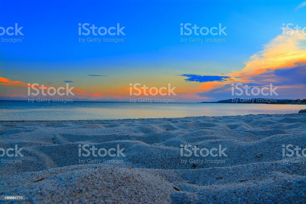 sunset in Maria Pia beach seen from the sand stock photo