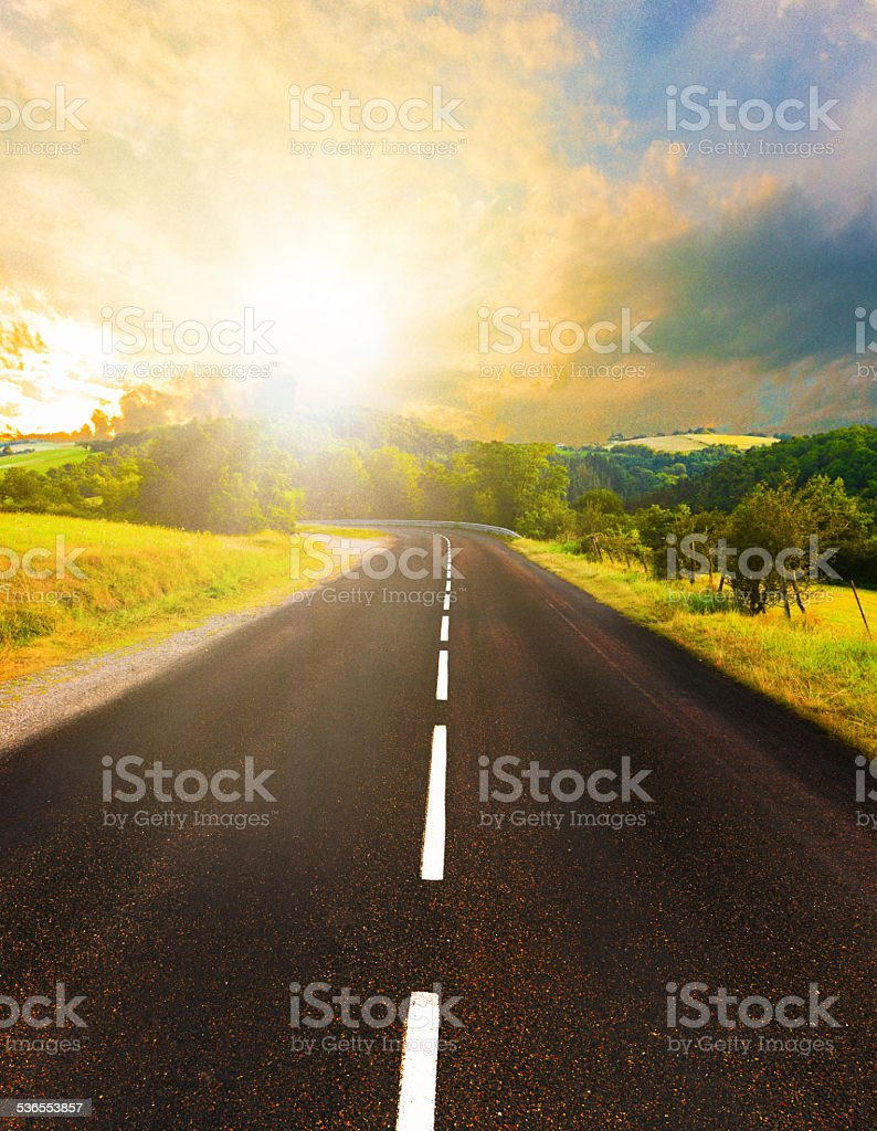 Sunset in nature with endless road leading towards forests stock photo