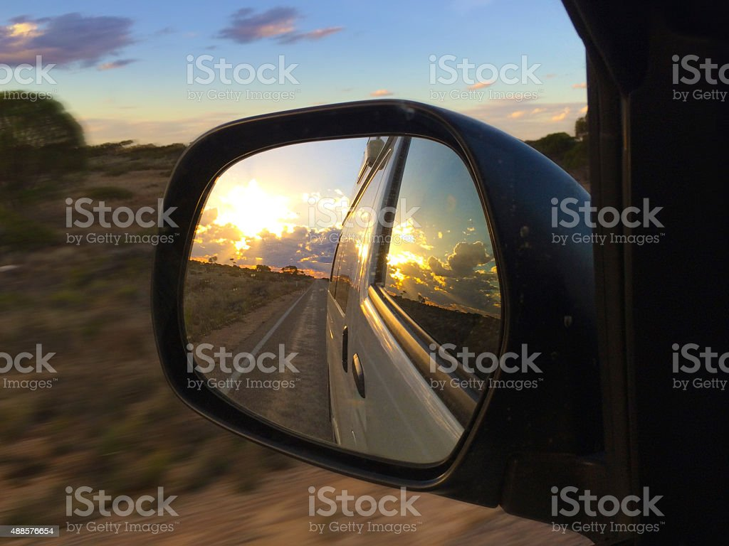 Sunset in rear view mirror stock photo