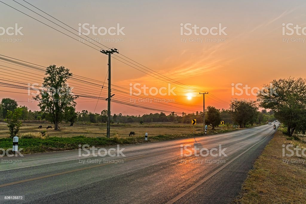 Sunset landscape ; Sunset on the road with traveller stock photo