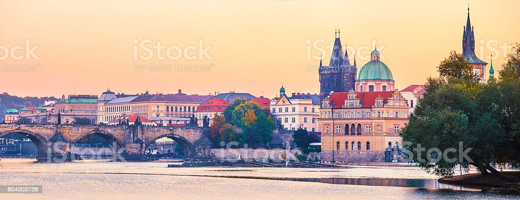 Sunset landscape view to Charles bridge on Vltava river in stock photo