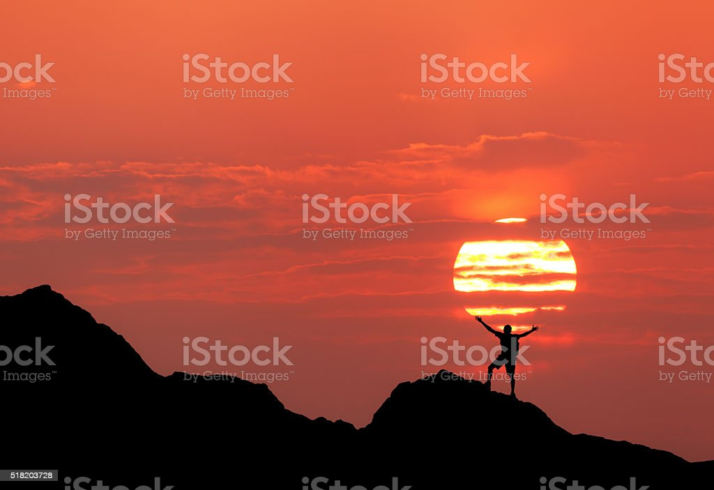 Sunset landscape with silhouette of a man with raised-up arms stock photo
