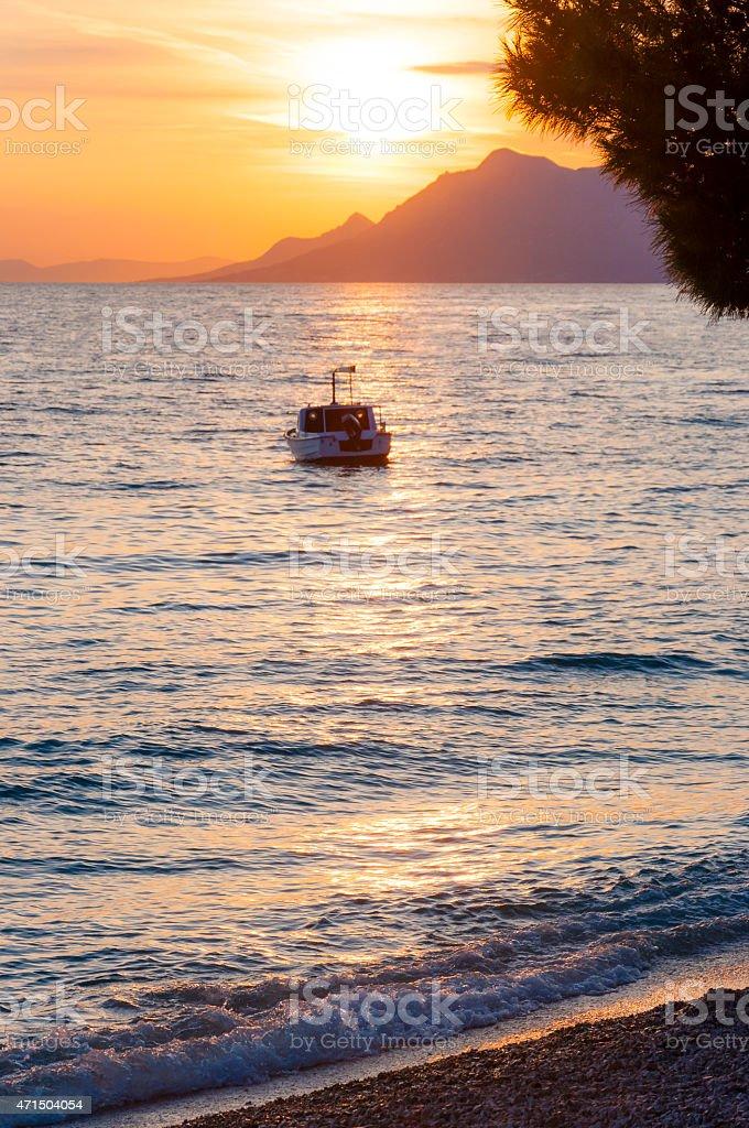 Sunset motorboat on the Adriatic sea beach in Makarska, Croatia stock photo