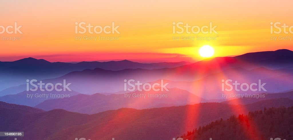 Sunset on a foggy mountain range stock photo